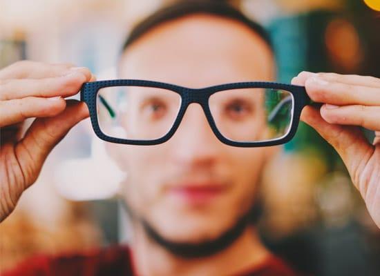 myope en train de mettre une lunette