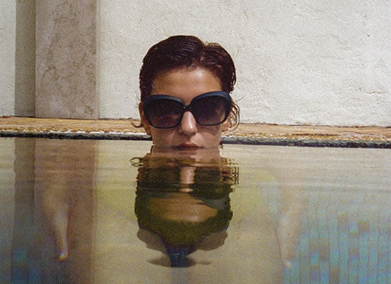 Femme avec des lunettes de soleil dans une piscine